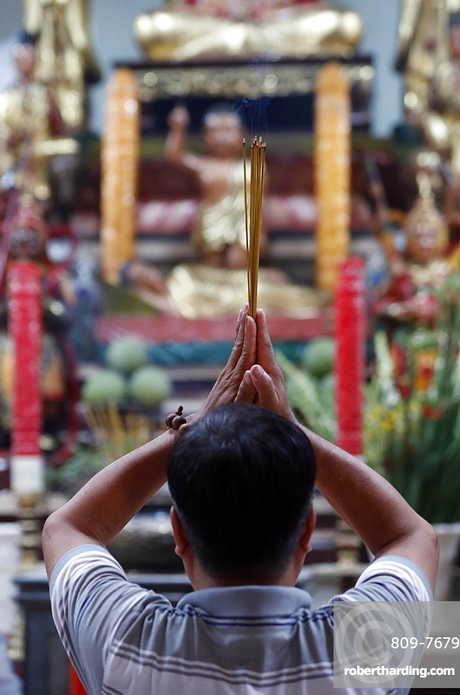 Man praying to the Buddha holding incense sticks, Tay An temple, Chau Doc, Vietnam, Indochina, Southeast Asia, Asia