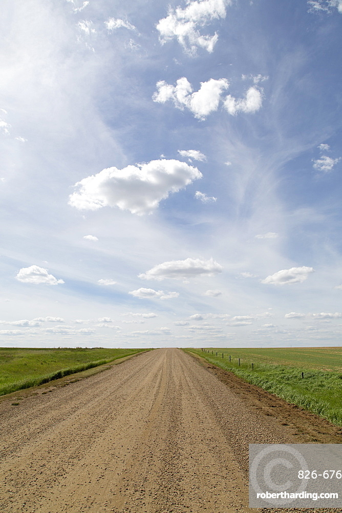 Clouds and blue sky over a dirt track in the Badlands of Alberta, near Drumheller, Alberta, Canada, North America
