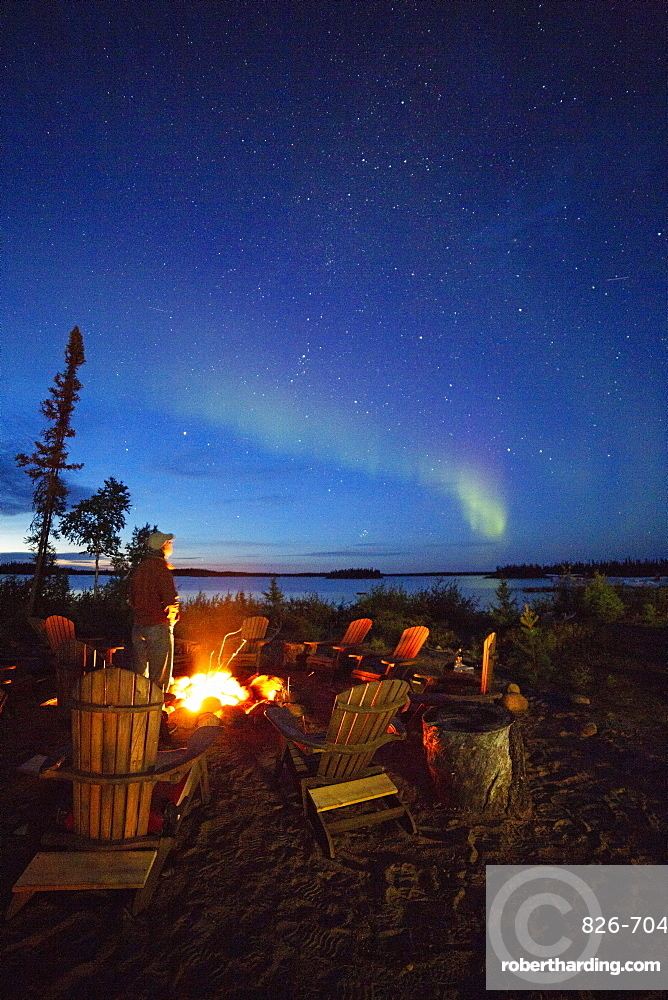 A man views the Northern Lights (aurora borealis) by a camp fire by Lake Egenolf in northern Manitoba, Canada, North America