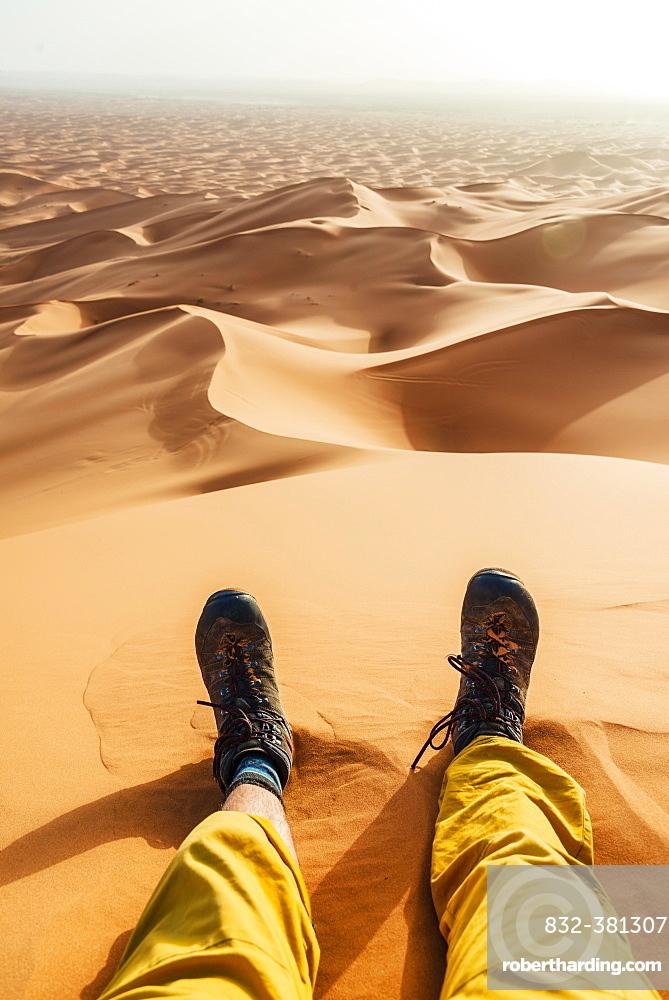 Legs with hiking boots in the sand, sand dune, desert, Erg Chebbi, Merzouga, Sahara, Morocco, Africa
