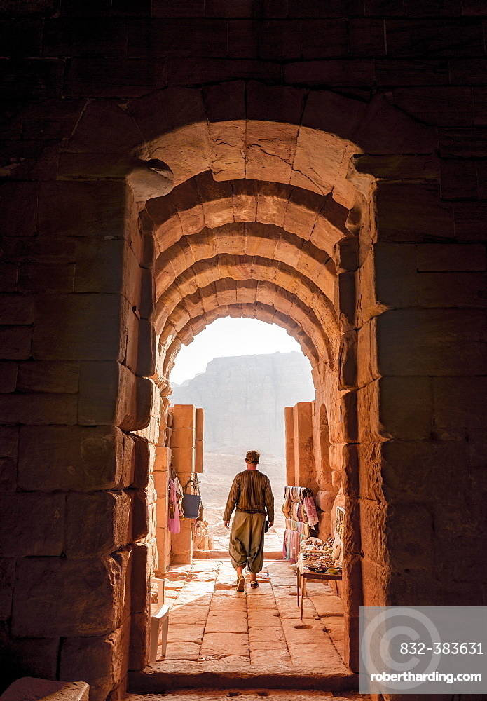 Tourist at the entrance to one of the royal tombs, rock carved mausoleum, Nabataean city of Petra, near Wadi Musa, Jordan, Asia