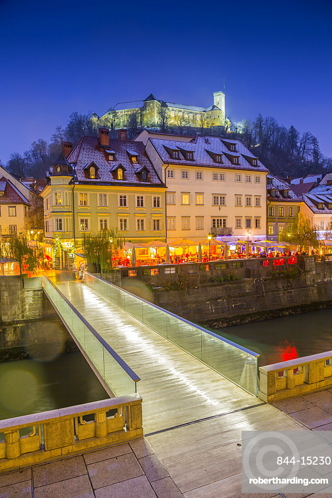 View of houses on the Ljubljanica River and Ljubljana Castle at dusk, Ljubljana, Slovenia, Europe
