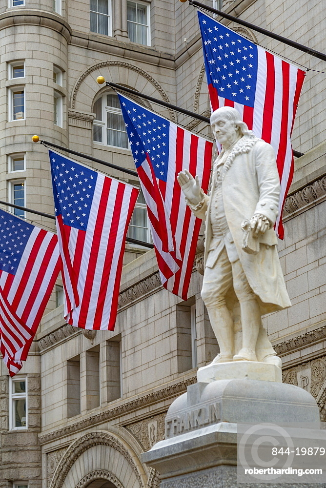 View of Benjamin Franklin statue and US flags in front of former Old Post Office Pavilion, Washington DC, District of Columbia, United States of America