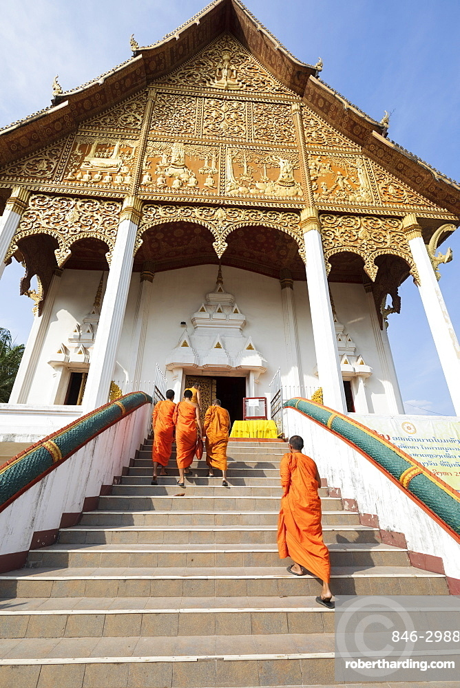 Buddhist monks climbing stairs to a temple at the Pha That Luang, Vientiane, Laos, Southeast Asia