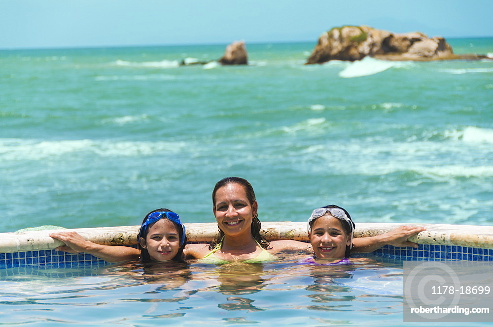 Portrait of family in swimming pool (8-9 years) (10-11 years), Humacao, Puerto Rico