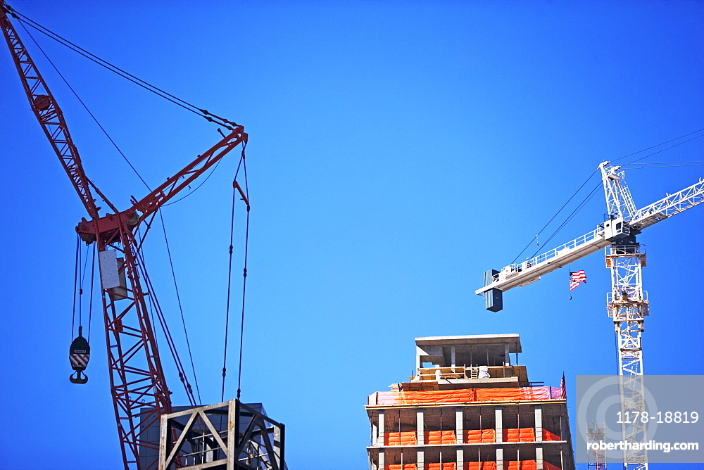 Cranes and high-rise under blue sky
