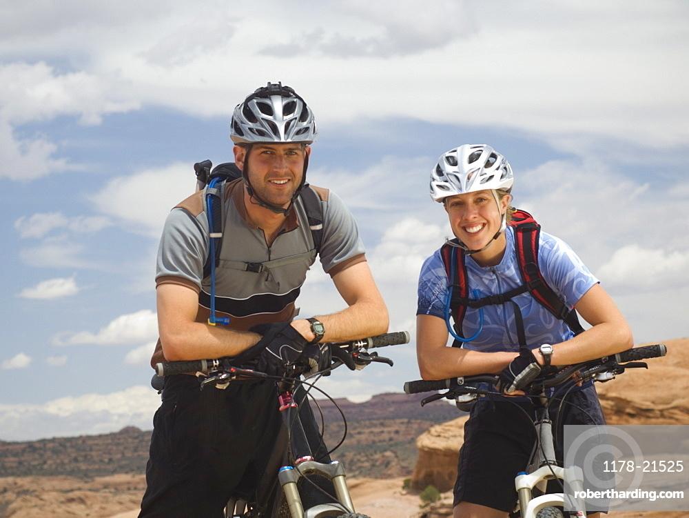 Couple sitting on mountain bikes