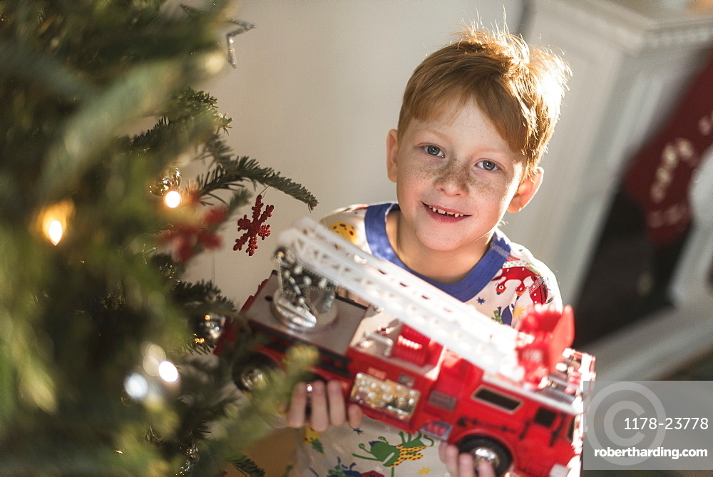 Portrait of boy (6-7) holding toy firetruck