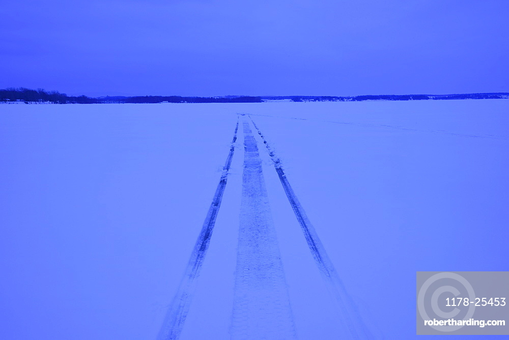 Snowmobile tracks on frozen lake, | Stock Photo