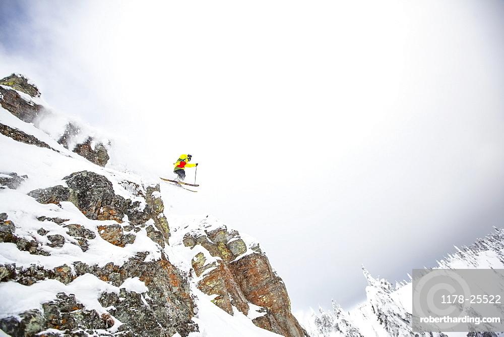 Skier jumping off rocky mountain, USA, Montana, Whitefish