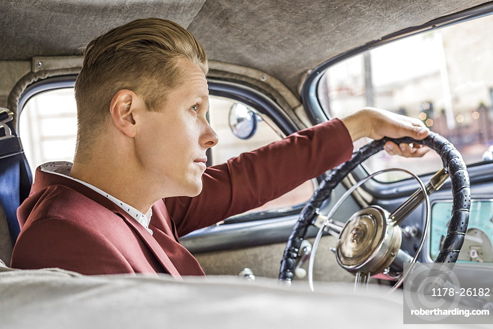 Blond man driving vintage car