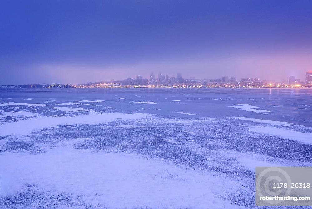 Ukraine, Dnepropetrovsk region, Dnepropetrovsk city, Dramatic sky over frozen river at dusk