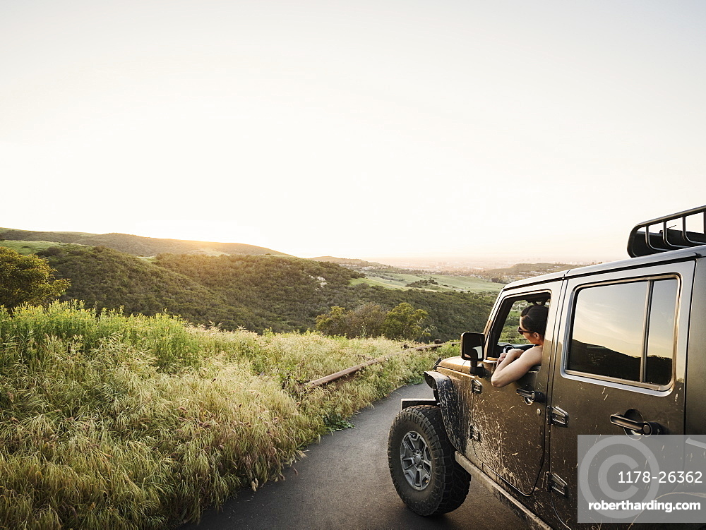 Woman in off road vehicle looking at sunset