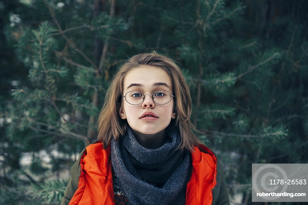 Teenage girl with glasses by pine tree