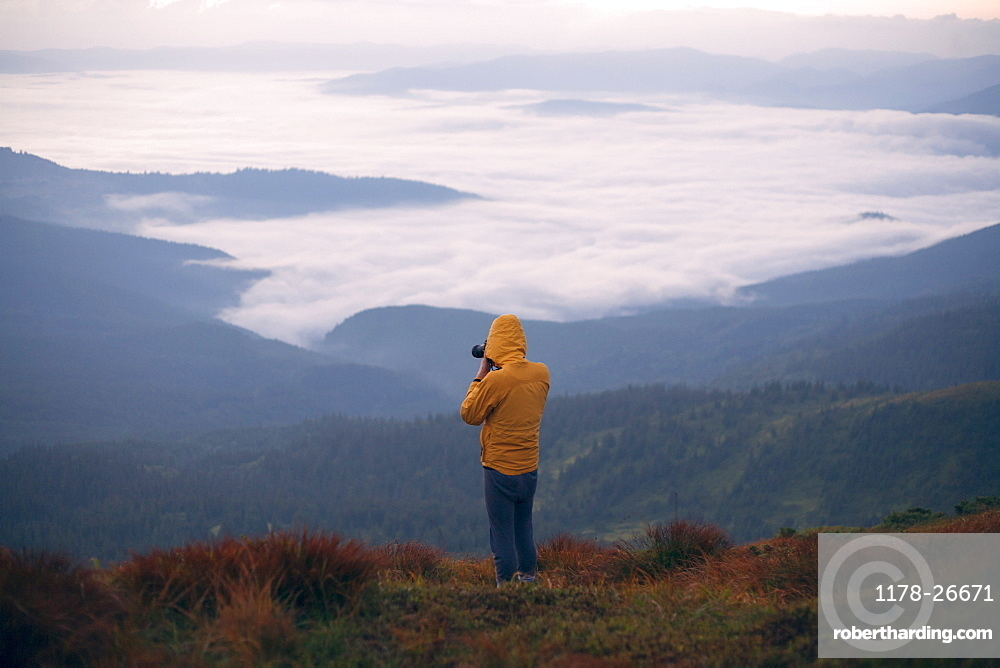 Man in yellow jacket taking photographs in the Carpathian Mountain Range