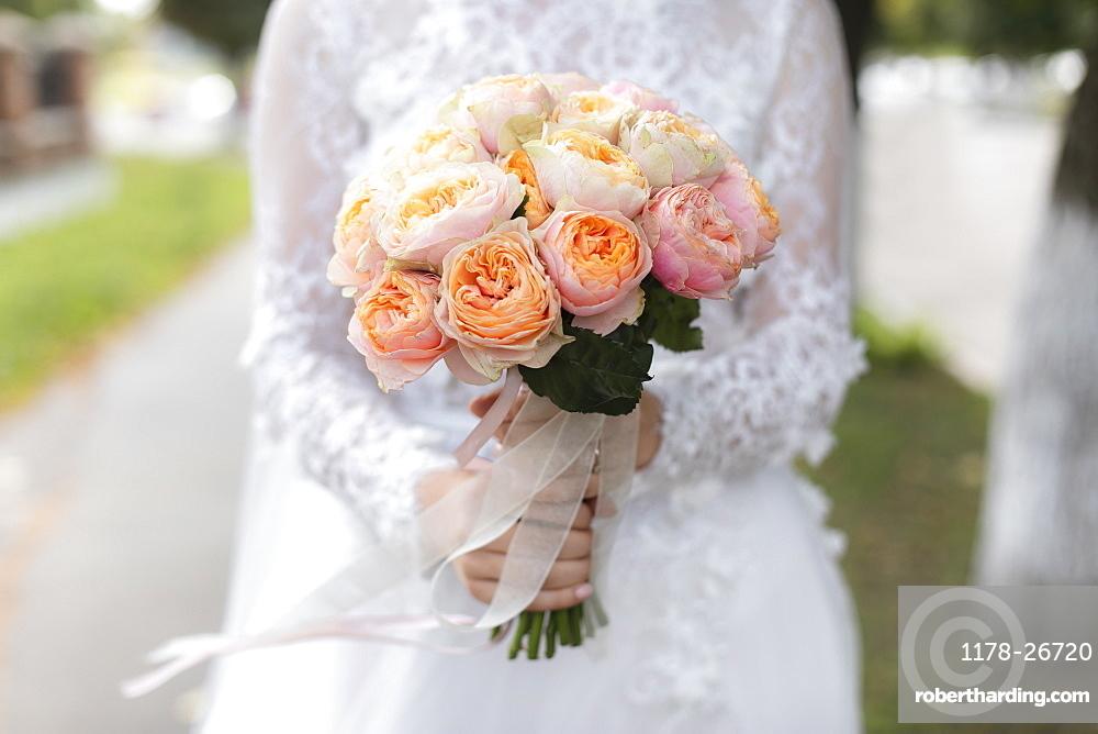 Hands of bride holding bouquet