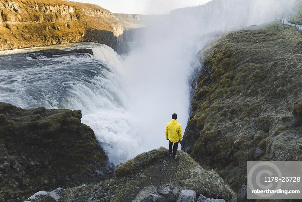 Hiker by Gullfoss waterfall in Iceland