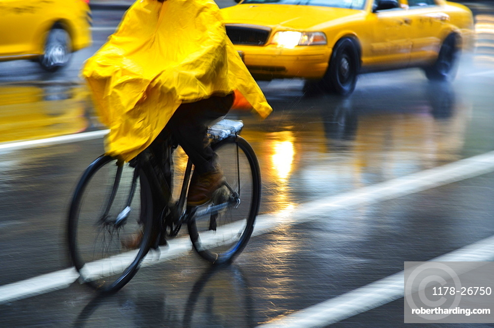 Cyclist in yellow poncho during rain in New York City, USA