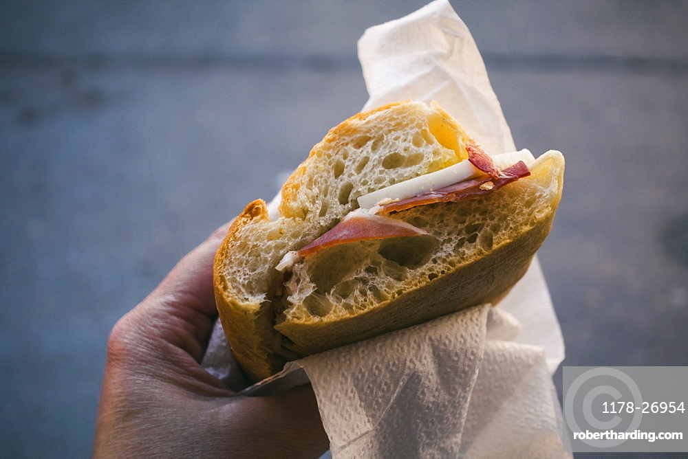Woman's hand holding pancetta and cheese sandwich