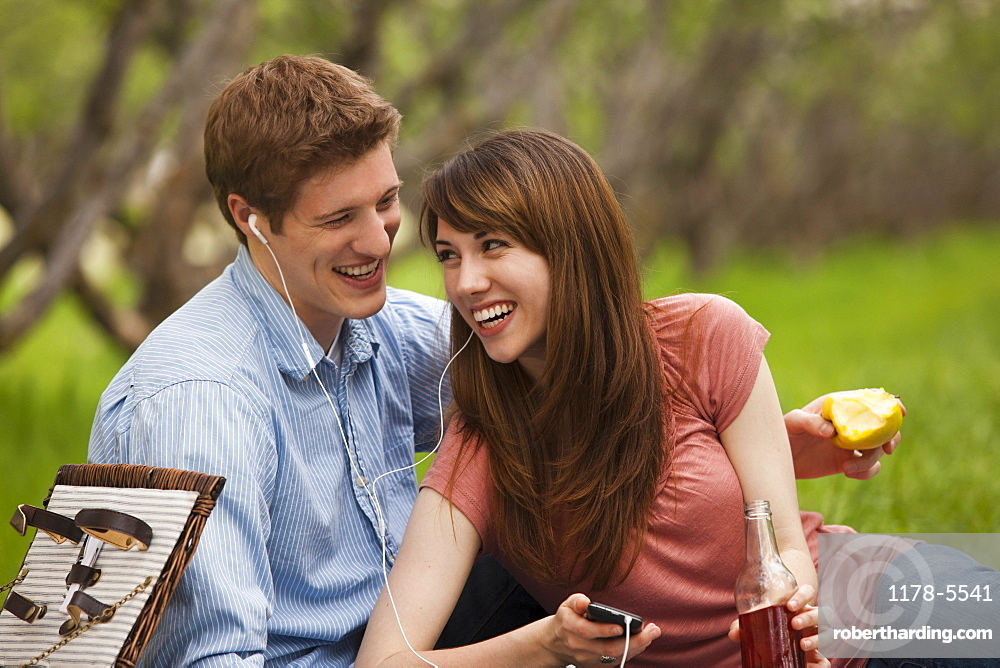 Young couple with mp3 player in orchard
