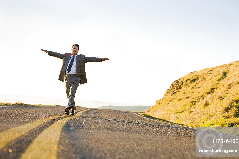 Businessman running on remote road