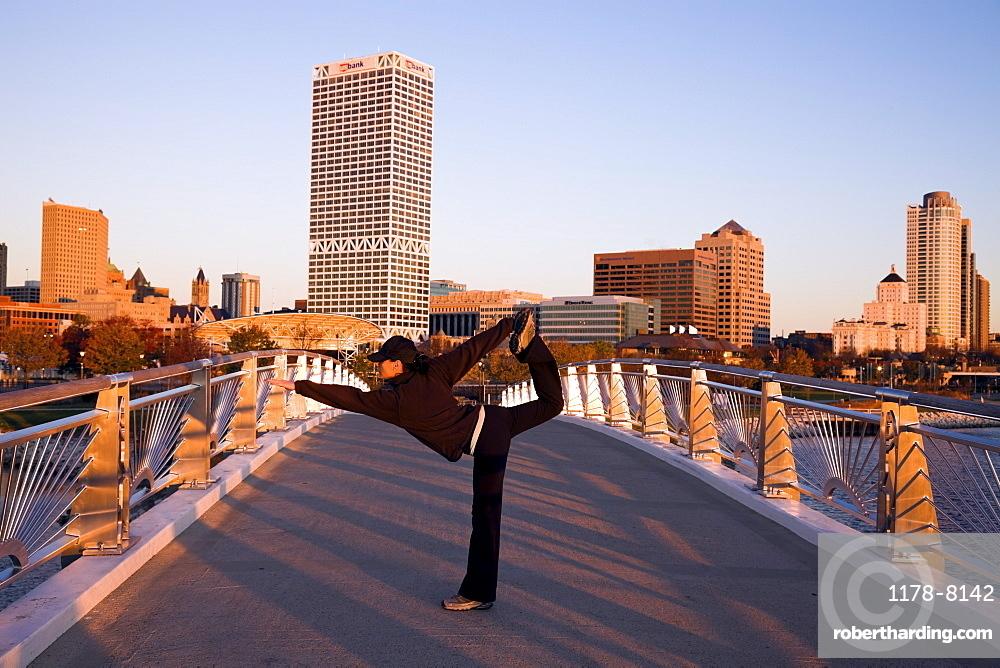 USA, Wisconsin, Milwaukee, Woman doing yoga on bridge in city