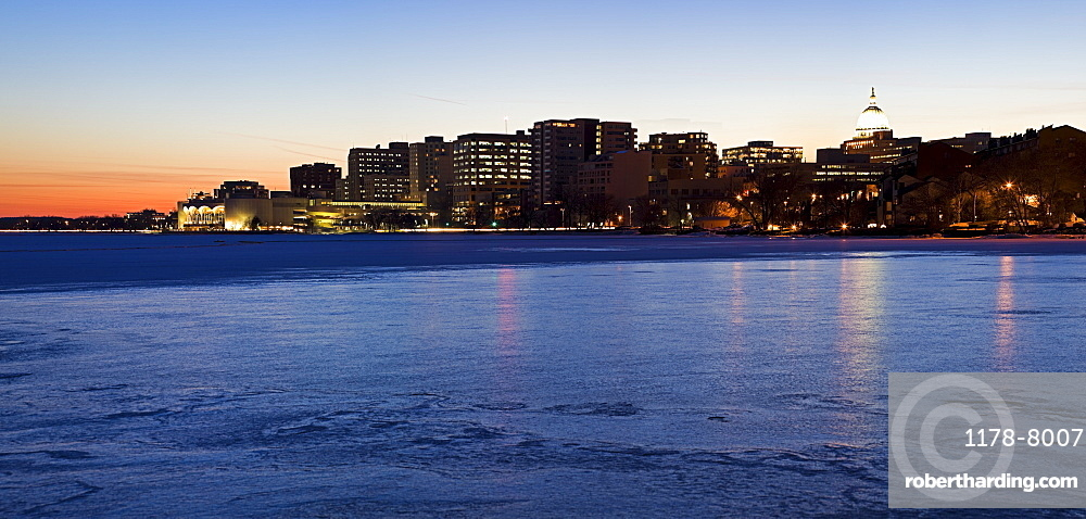 USA, Wisconsin, Madison skyline across frozen lake at dusk