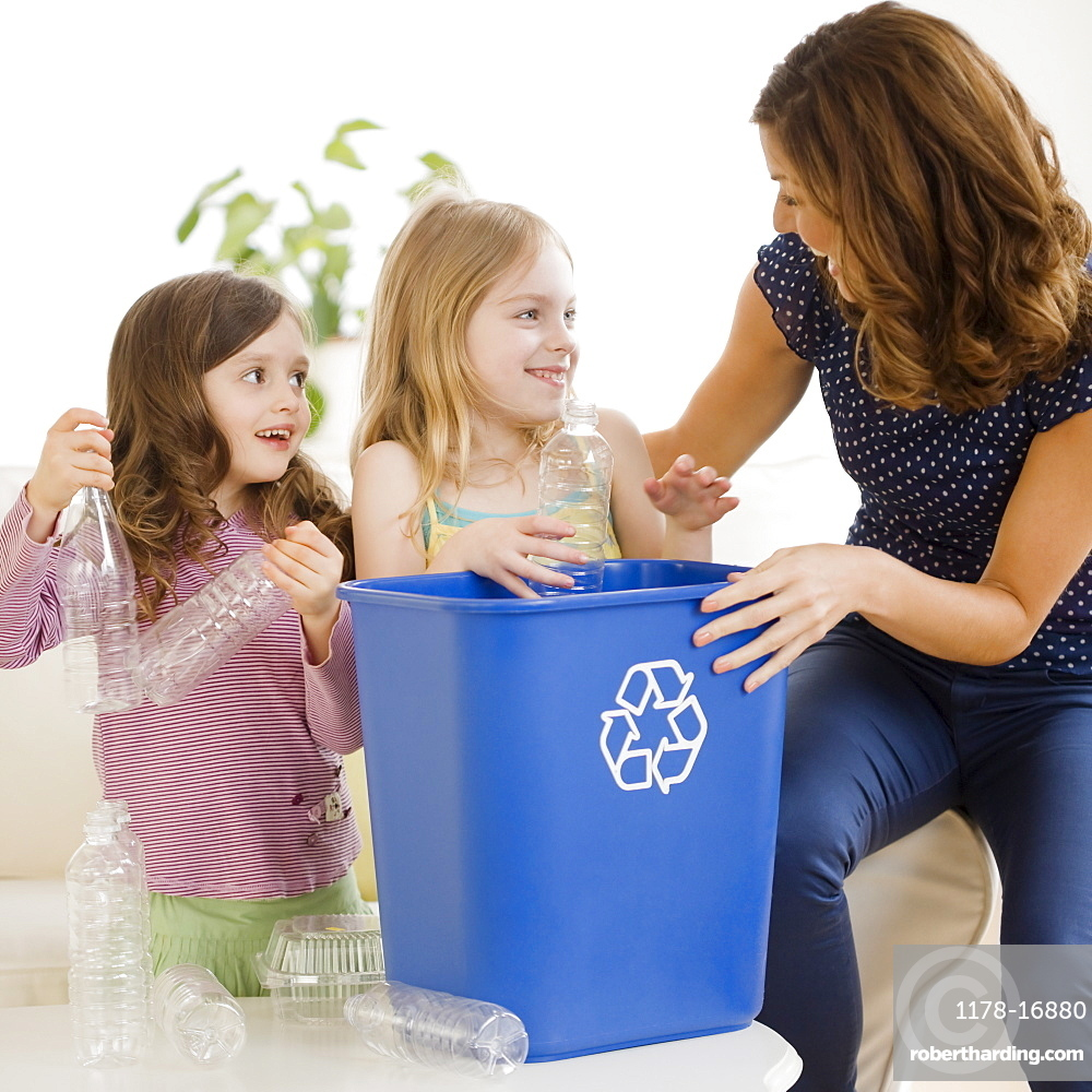 Mother and daughters filling recycling bin
