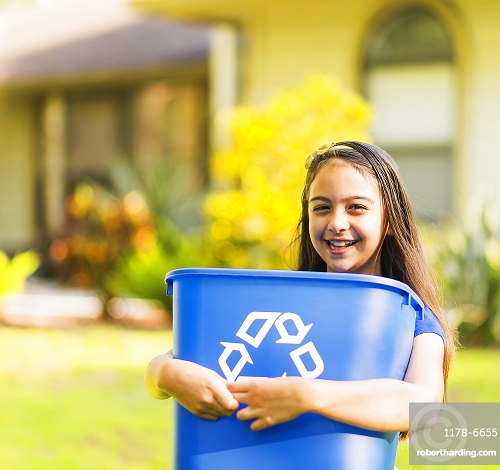 Portrait of girl ( 8-9) holding recycling bin