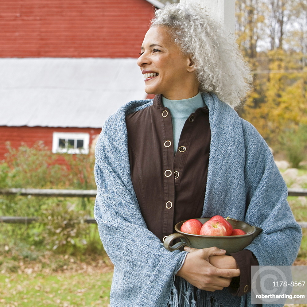 Woman holding bowl of apples