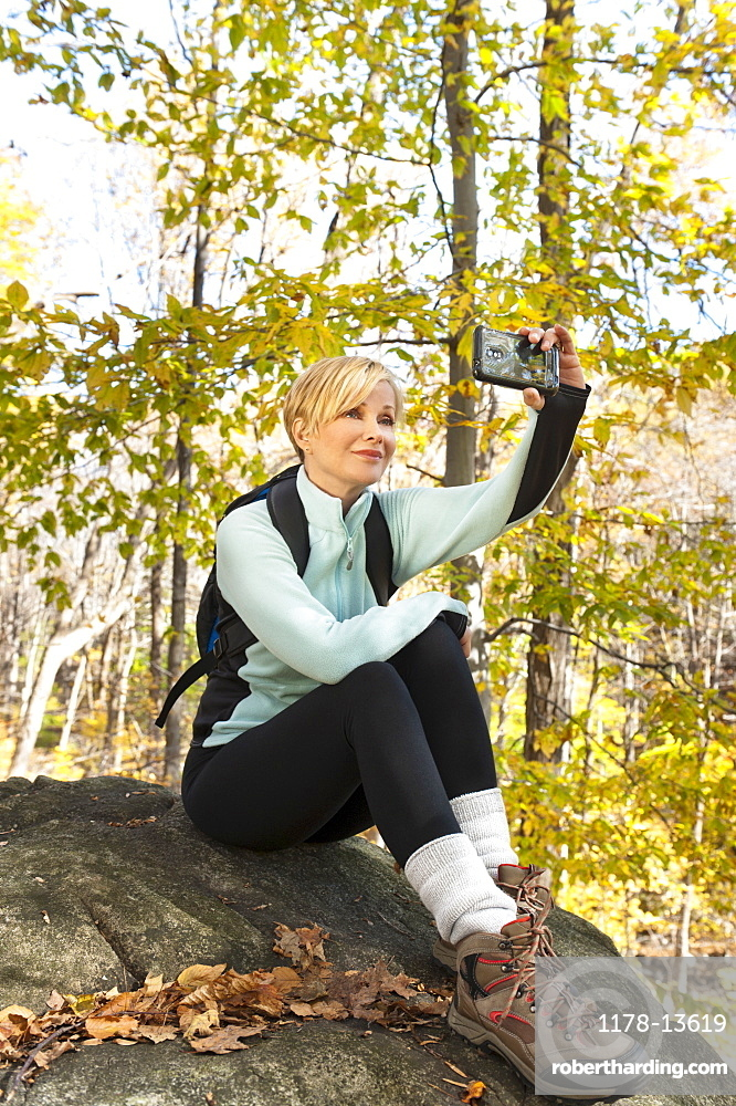 Female hiker photographing self on rock in forest