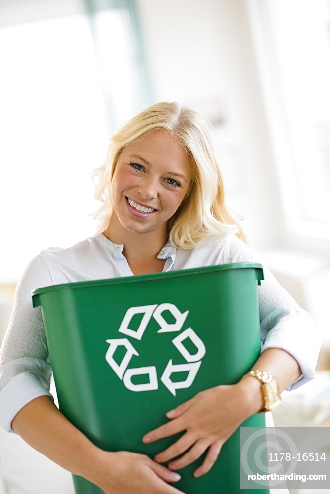 Portrait of young woman holding recycling bin