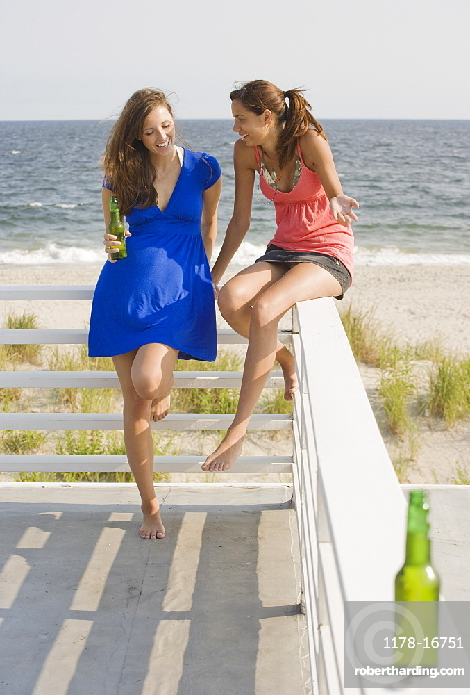 two women leaning on railing stock photo