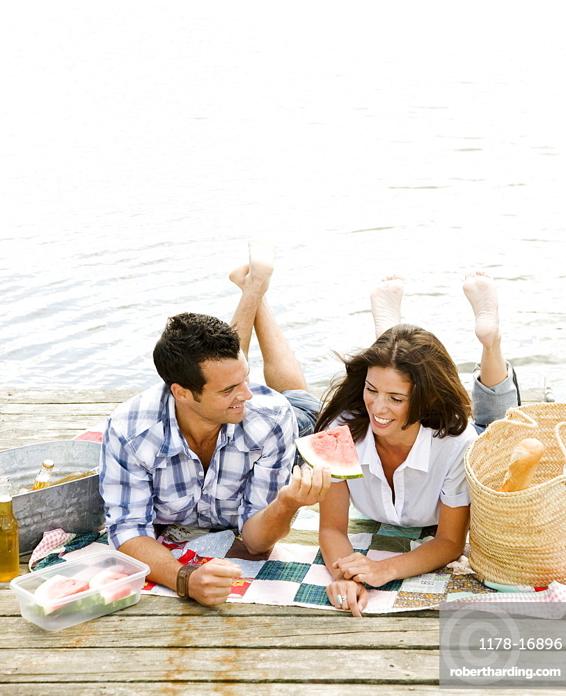 Couple picnicking on dock