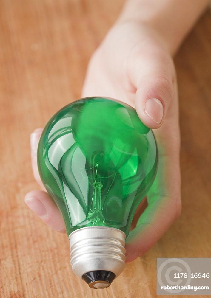 Woman holding green light bulb