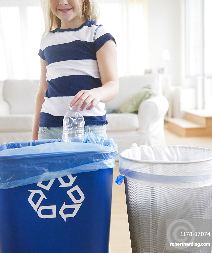 USA, New Jersey, Jersey City, Girl (8-9) putting plastic bottle into recycling bin