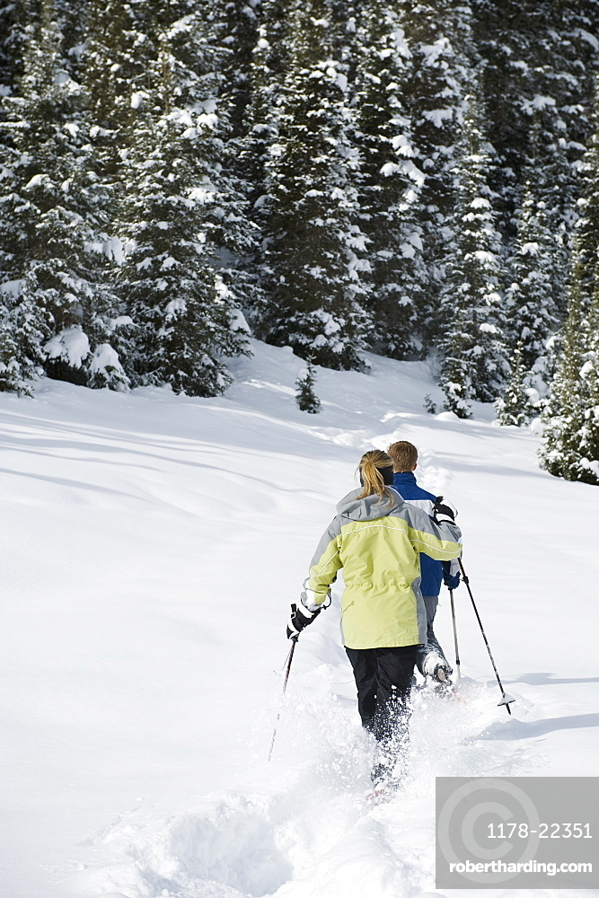 A couple snow shoeing