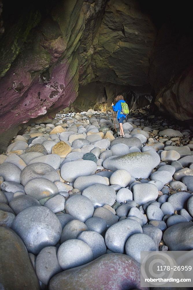 Teenage boy exploring cave with rocks in La Jolla, California