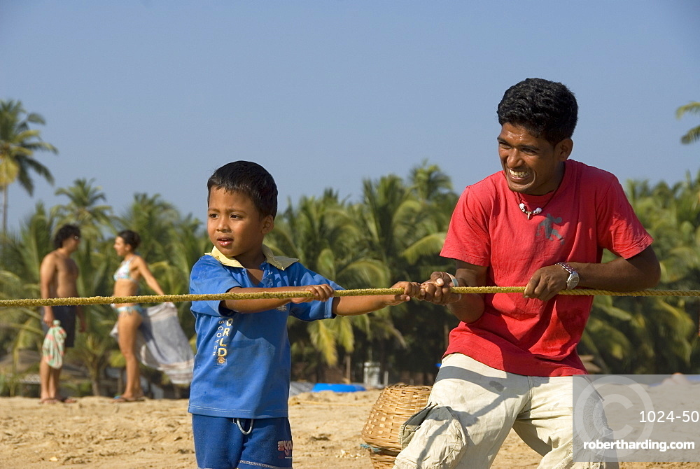 Man And Boy Hauling In Fishing Net From The Beach Goa India