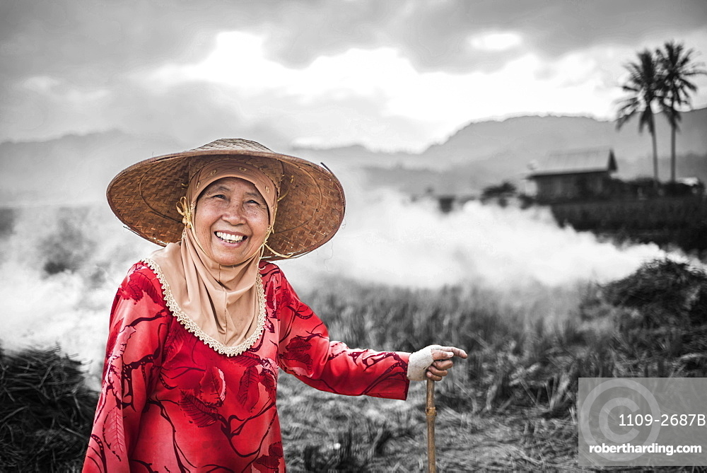 Portrait of a farmer burning crops in rice paddy fields, Bukittinggi, West Sumatra, Indonesia, Southeast Asia, Asia