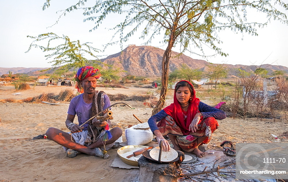 Hindu girl cooking while her father plays musical instrument in Pushkar, Rajasthan, India, Asia