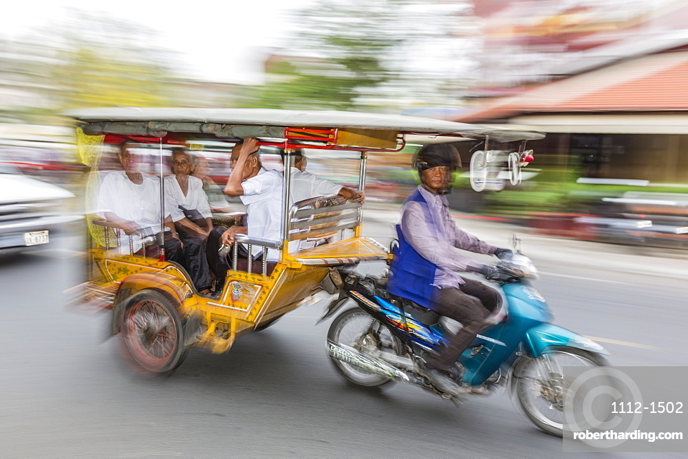 Motion blur image of a tuk-tuk in the capital city of Phnom Penh, Cambodia, Indochina, Southeast Asia, Asia