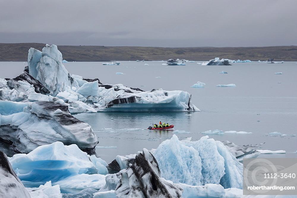 Boat amongst calved ice from the Breidamerkurjokull glacier in Jokulsarlon glacial lagoon, Iceland, Polar Regions