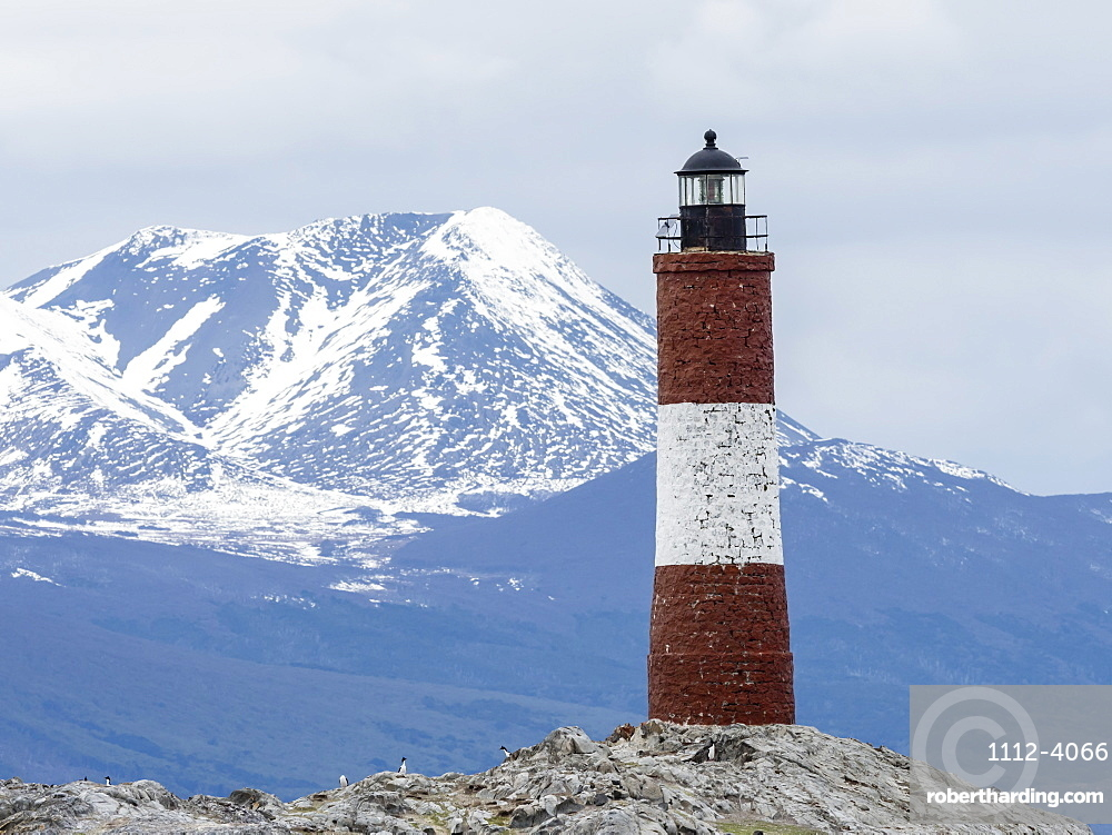 Lighthouse with Andes Mountains in the background on a small islet in the Beagle Channel, Ushuaia, Argentina.