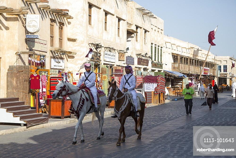 Police officers on horseback patrol at Souq Waqif, Doha, Qatar