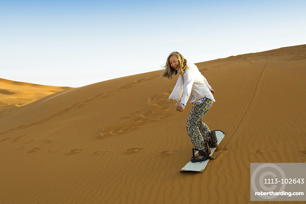 young woman with snowboard, sand | Stock Photo