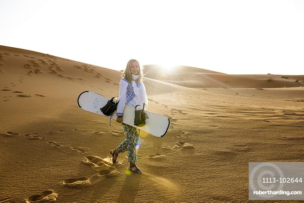young woman with snowboard, sand dunes near Merzouga, Erg Chebbi, Sahara Desert, Morocco, Africa