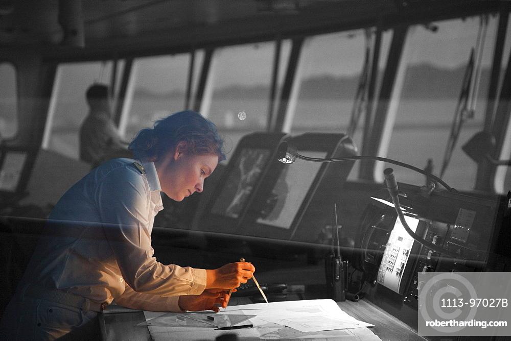 Safety Officer Claudia Kempkes charting course on bridge of cruise ship MS Deutschland (Reederei Peter Deilmann) at dawn, Puerto Vallarta, Jalisco, Mexico