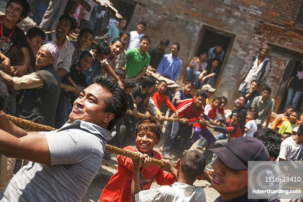 Young people pulling the strings to hoist the mast at the traditional Bisket Jatra Festival in Napalese New Year, Bhaktapur, Nepal