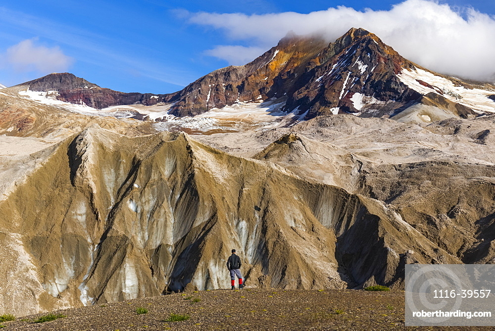A man is dwarfed by the jagged, ash-covered Knife Creek Glaciers and Trident Volcano in the Valley of Ten Thousand Smokes in Katmai National Park; Alaska, United States of America
